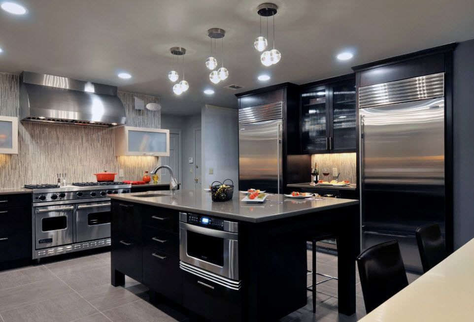 Black noble kitchen set facades and steel glancing appliances