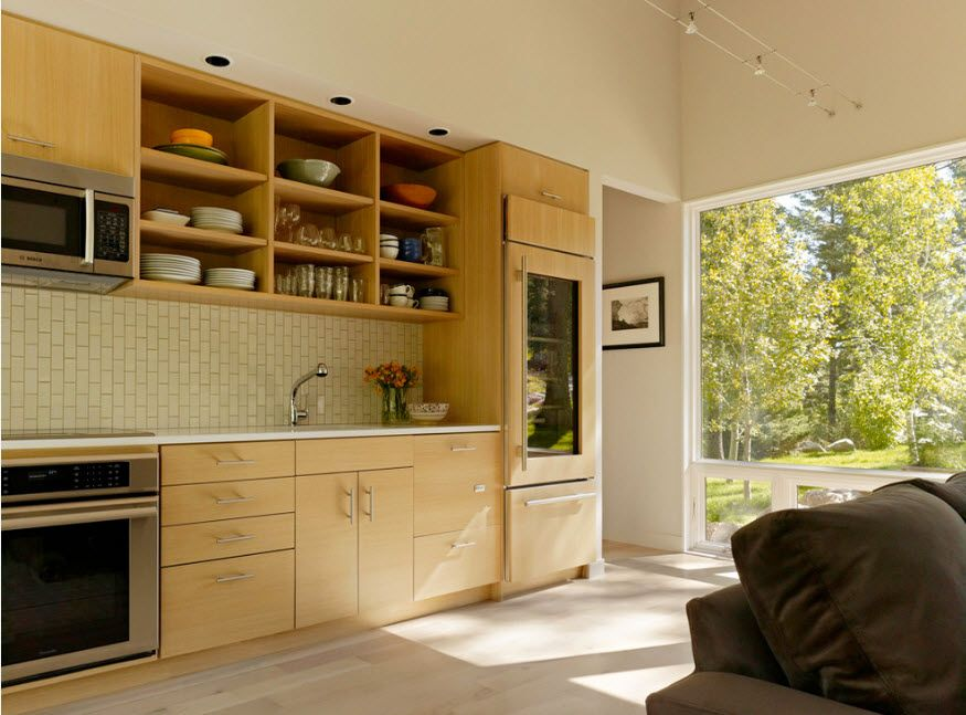Light wooden kitchen furniture set next to the panoramic entrance