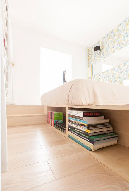Wooden platform of the bed and the open shelf for the books