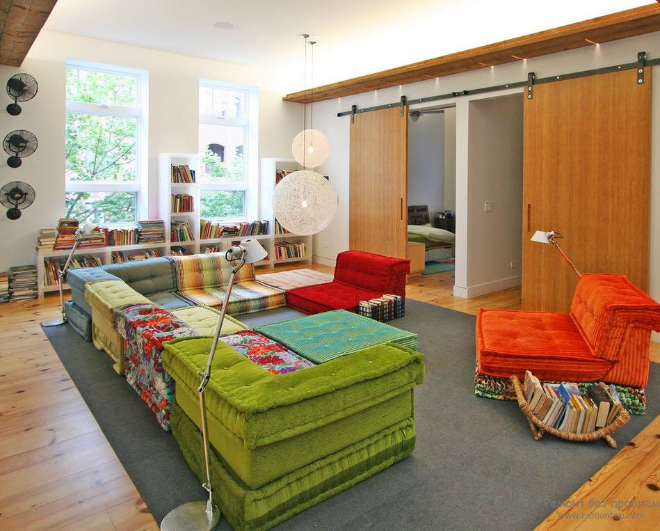 Green and red furniture in the pastel colored bright and light room with sliding doors