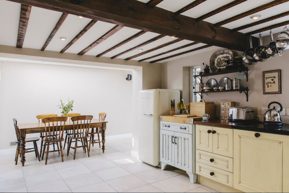 Open dark wooden beams in the large light designed Mediterranean kitchen with dining zone