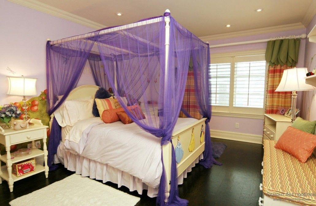 Bed with purple tulle on the white canopy frame