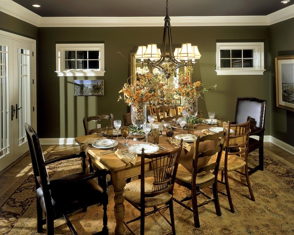Large classic decorated dining room with dark olive painted walls