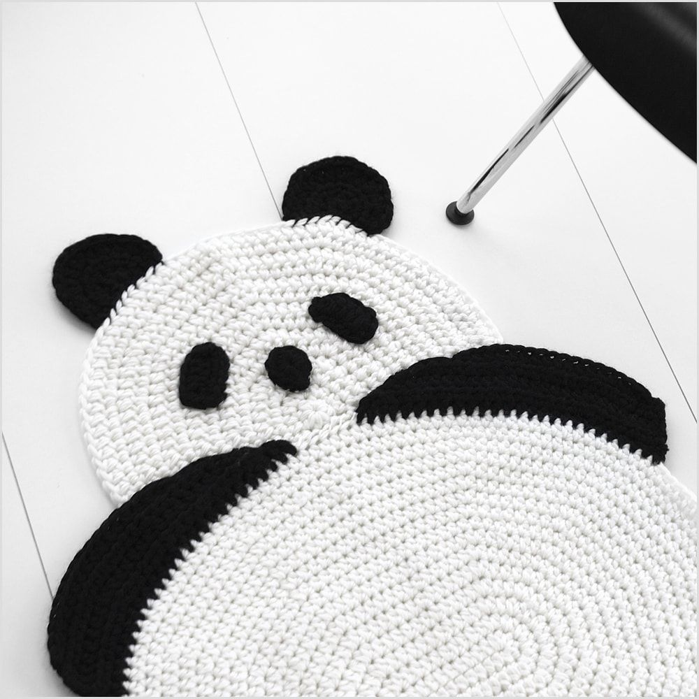 Knitted panda as the small decorative rug