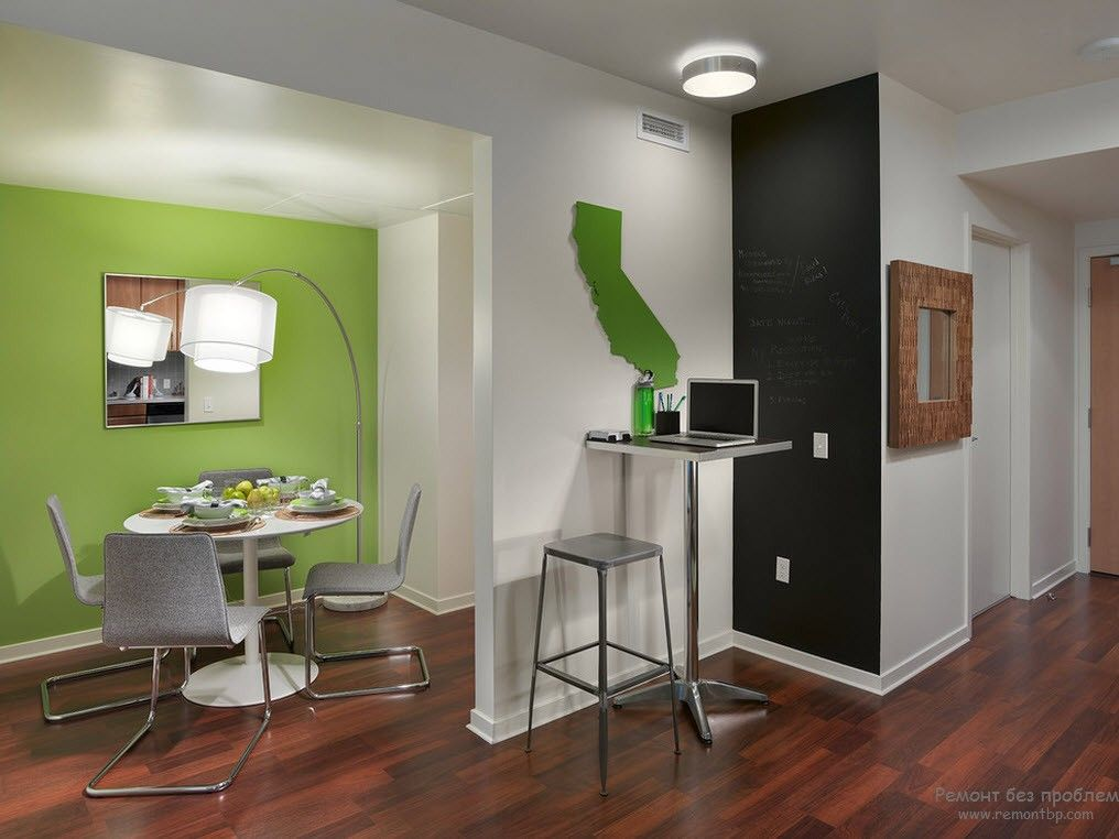 Mint green accent wall in the studio apartment for the dining zone