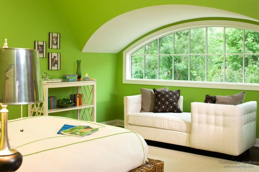 Green painted attic premises of the bedroom with white upholstered furniture