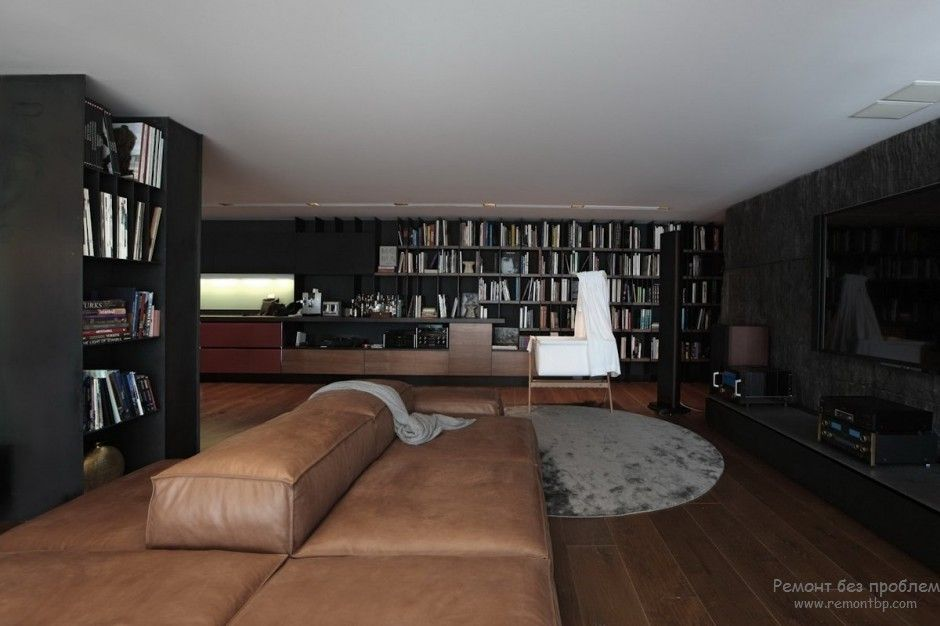 Luxurious large library with the leather upholstered furniture and big fluffy rug