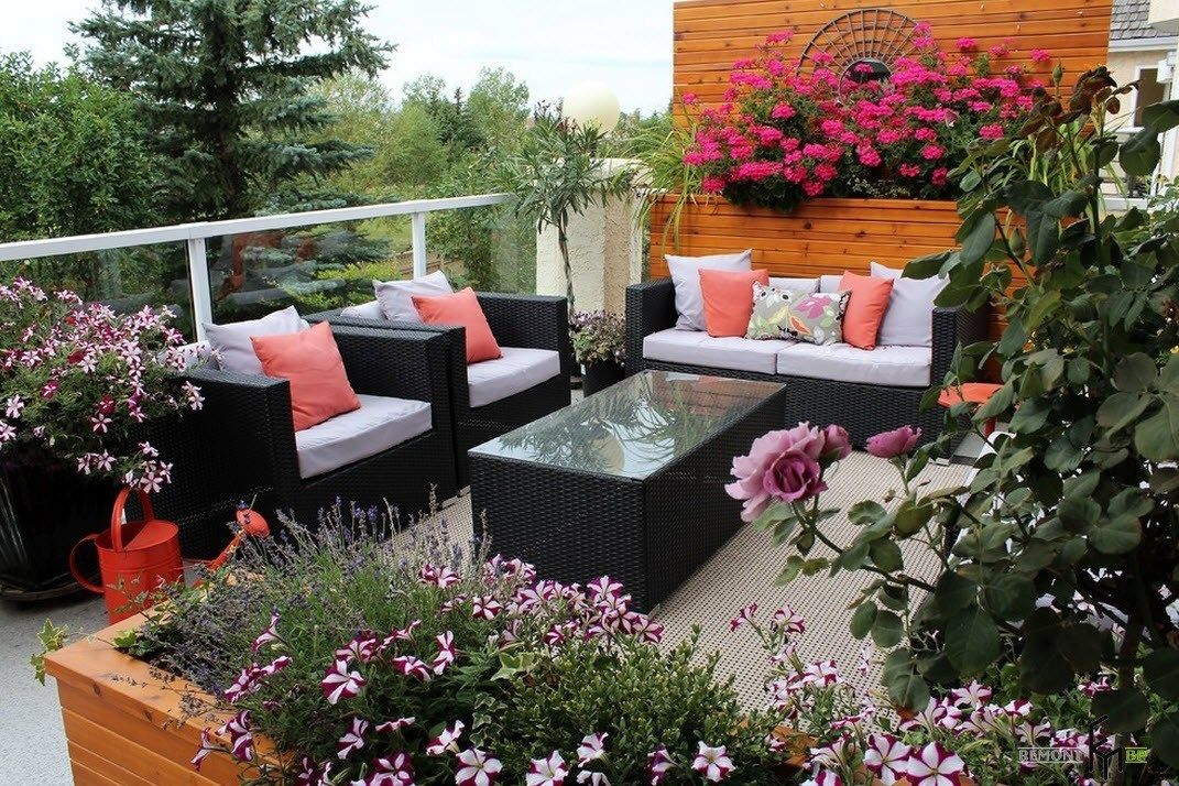 Patio furniture outdoor. Reviewing Types with Photo. Black wicker armchairs and sofa and the coffee table in the center with mirror surface