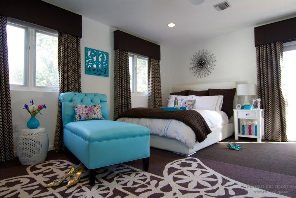 Turquoise armchair in the bedroom with dark curtains