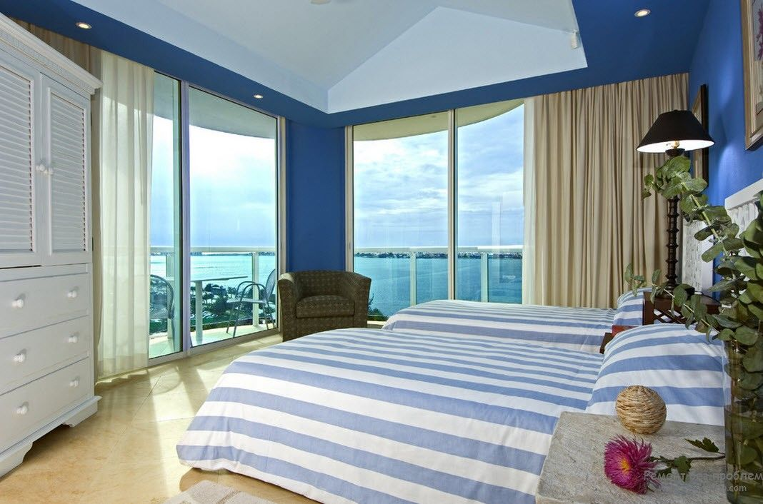 Coupl of blue shades mix harmonically in the bedroom with the ocean view through panoramic windows