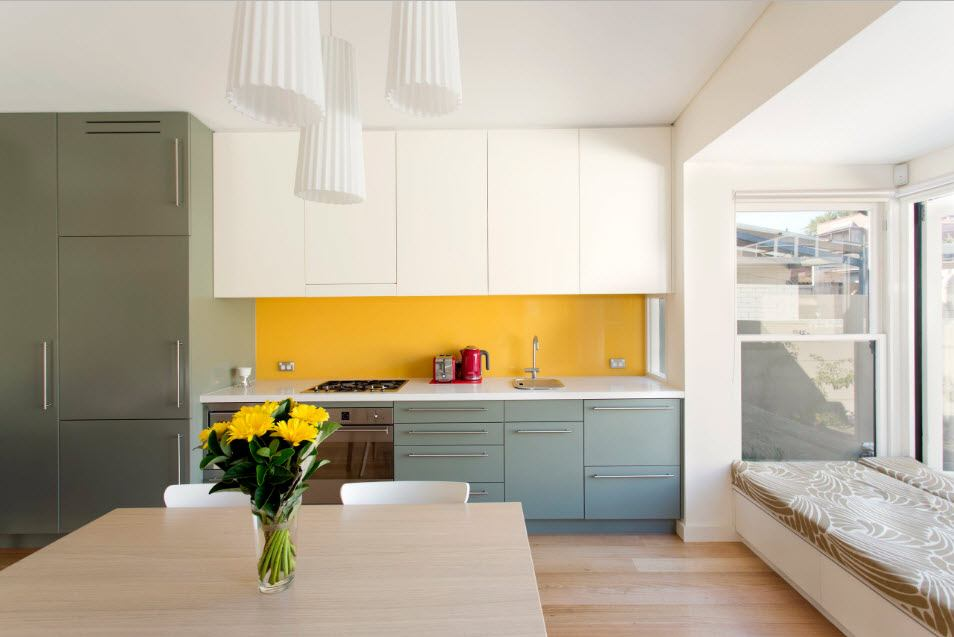 Yellow splashback and creamy facades of the kitchen furniture set in the hi-tech styled interior