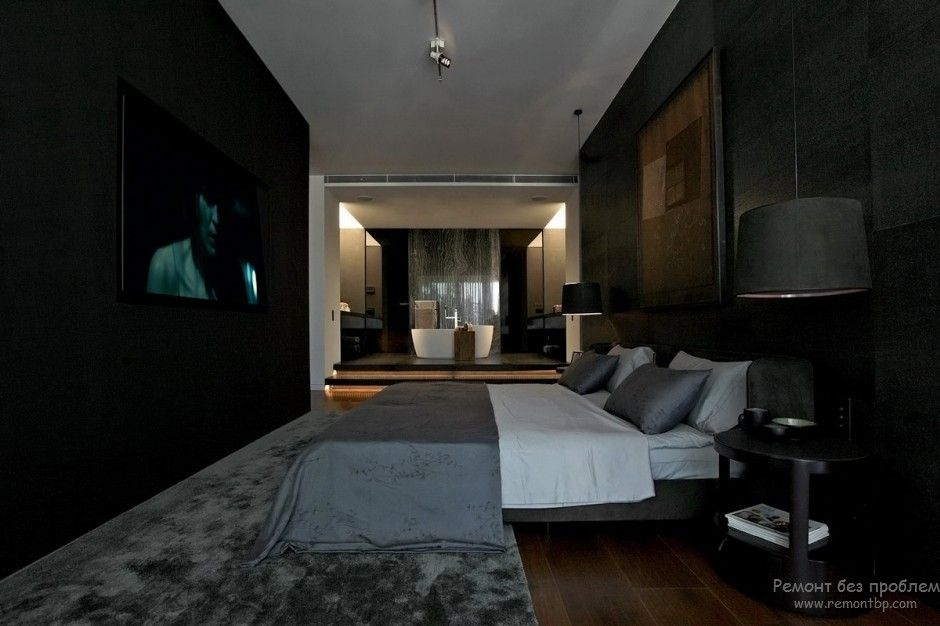 Unusual dark toned bedroom with absolutely ebony accent wall in front of the bed