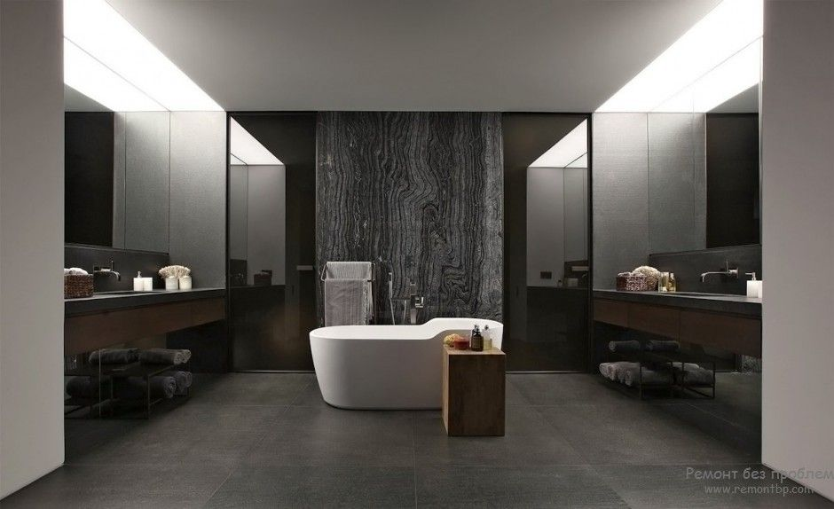 Open layout of spectacular dark tones bathroom with white bathtub