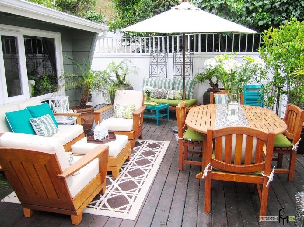 Patio furniture outdoor. Reviewing Types with Photo. Light wooden furn at the dark wooden platform of the resting zone