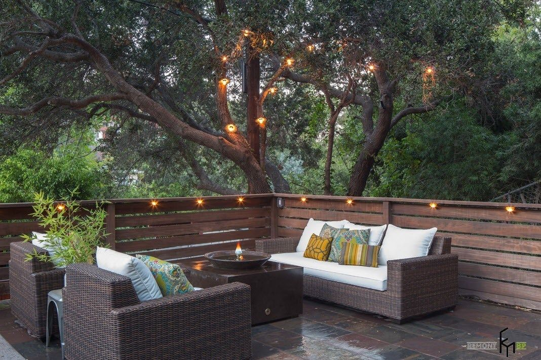Patio furniture outdoor. Reviewing Types with Photos. Wooden fence and the wicker furniture with white upholstery