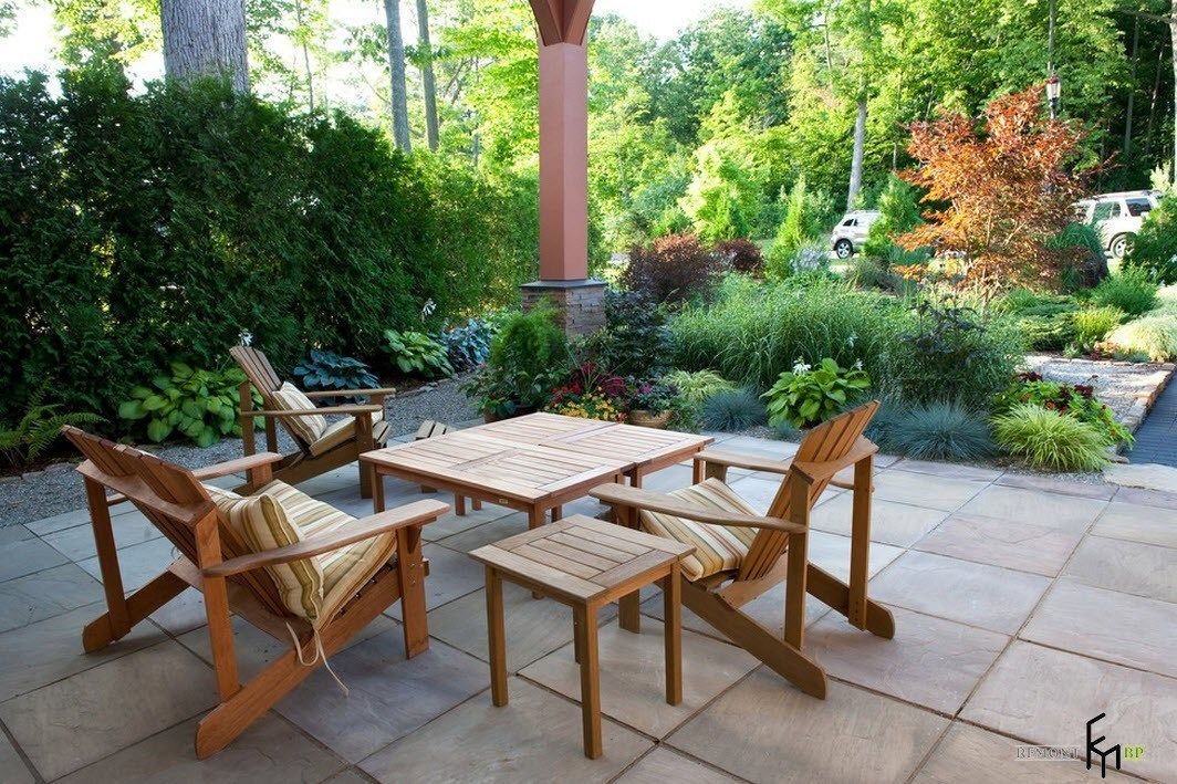 Patio furniture outdoor. Reviewing Types with Photo. Light wooden furn amonf the abundance of greenery at the backyard