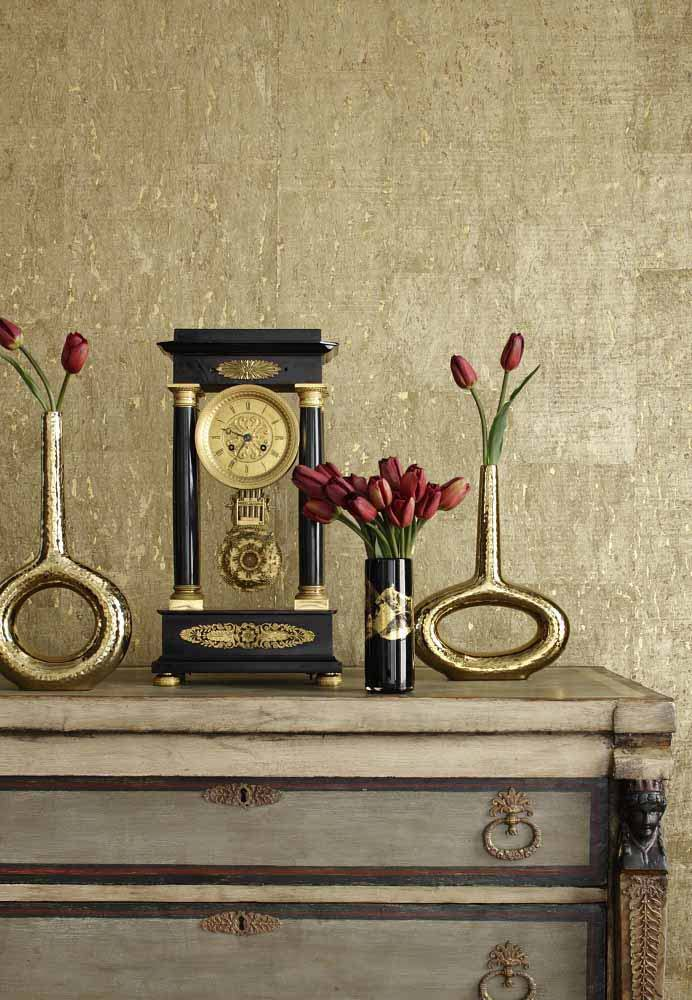 Mantelshelf with decorative elements at the background of golden gray cork wallpaper