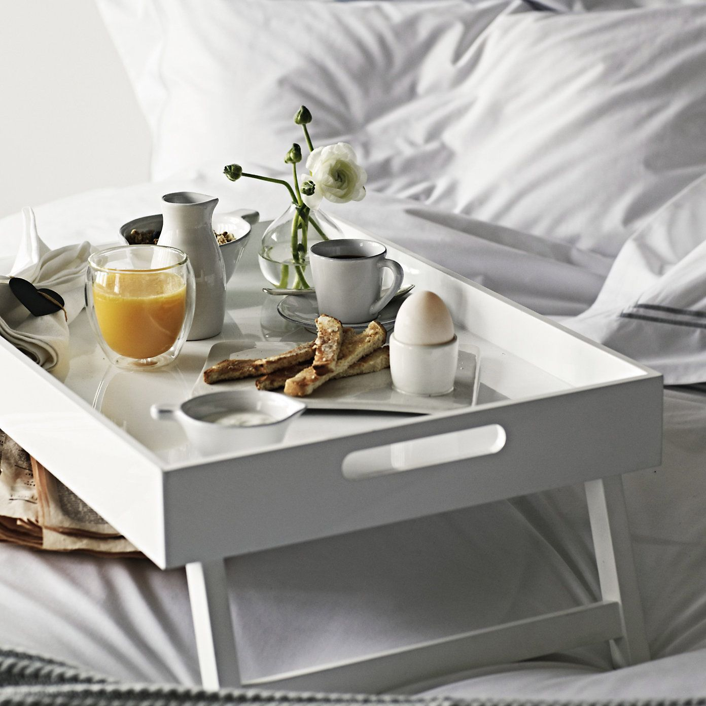 Overbed Table (Bed Tray). Expanding Functionality Element in Modern Home. White unit in the very same light interior atmosphere