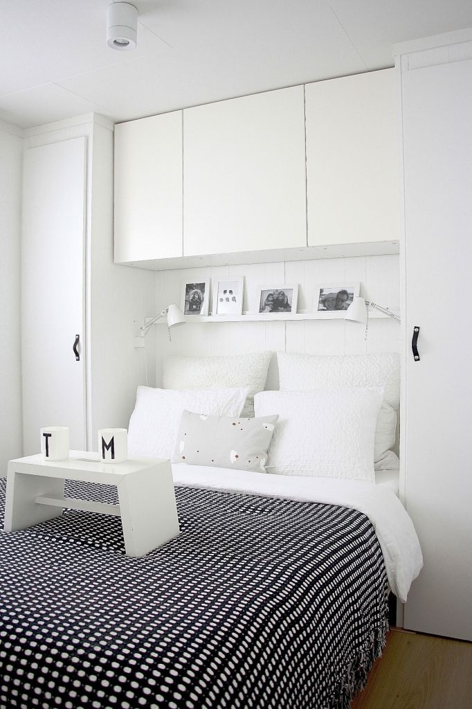 Overbed Table (Bed Tray). Expanding Functionality Element in Modern Home. Hi-tech white colored interior design with black striped bedding