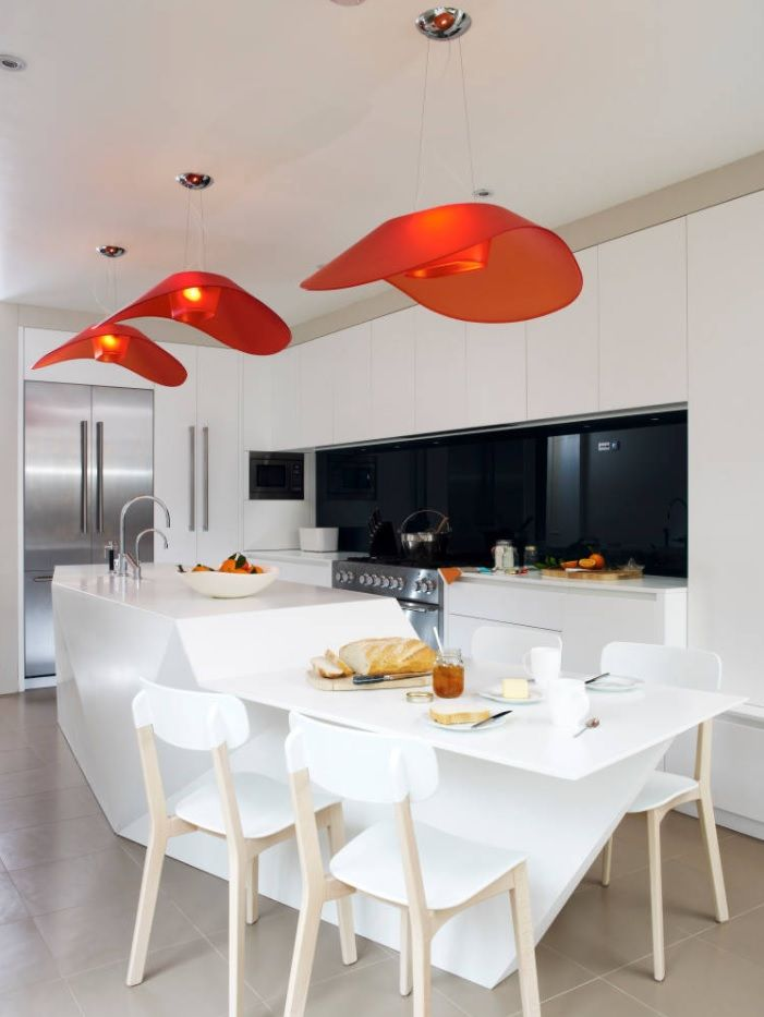 Modern designed matted white kitchen with red glass lampshades