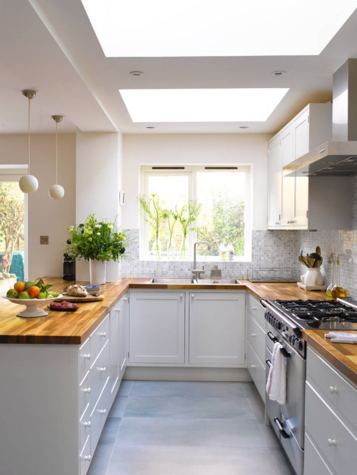 Butcher Block Countertop in Modern Kitchen Interior. U-shaped kitchen with wooden tops and functional utilization of widow space