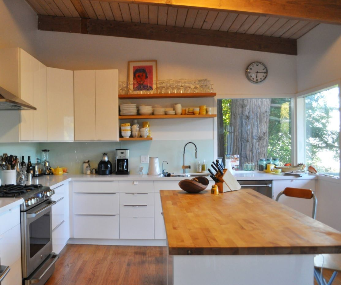 Butcher Block Countertop in Modern Kitchen Interior. Slanting ceiling and the minimalistic rustic style for the striking example of kitchen design