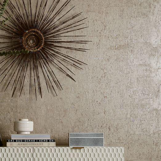 Sunburst decorative element at the background of neutral gray cork wallpaper