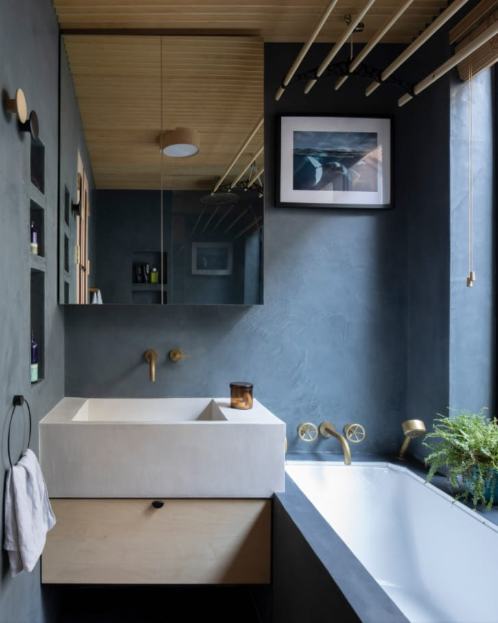 DIY Bathroom Remodel Ideas. Detailed Step by Step Instruction. Ultramodern dark blue interior in the small space with large sink and full-fledged bathtub