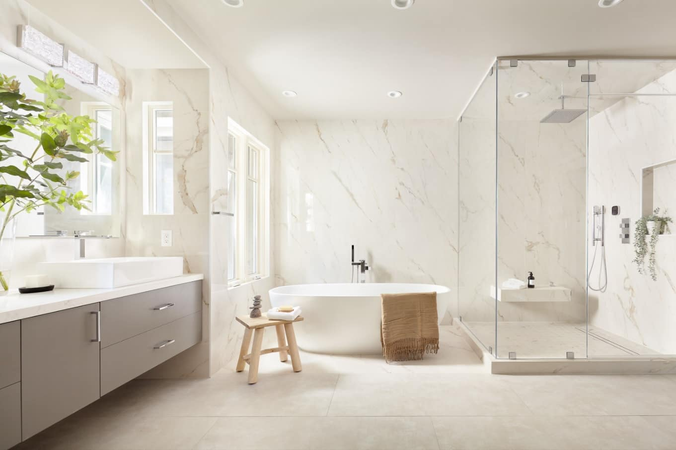 Marble cladded bathroom in Scandinavian style with eggshell bathtub, large classic wooden vanity and glass shower