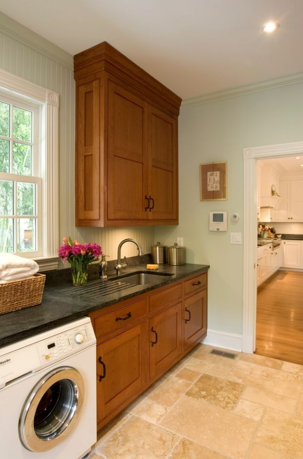 Laundry & Kitchen Functional Space Combination. Oak furniture set and dark granite countertop in the rustic styled premise