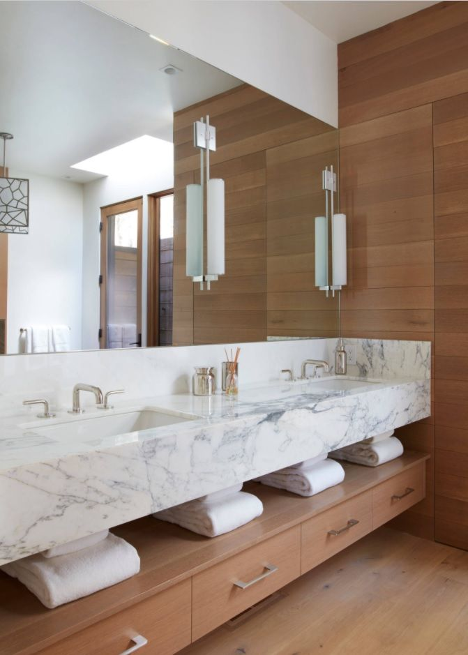 Unique design of the bathroom with continuous mirror and large marble sink