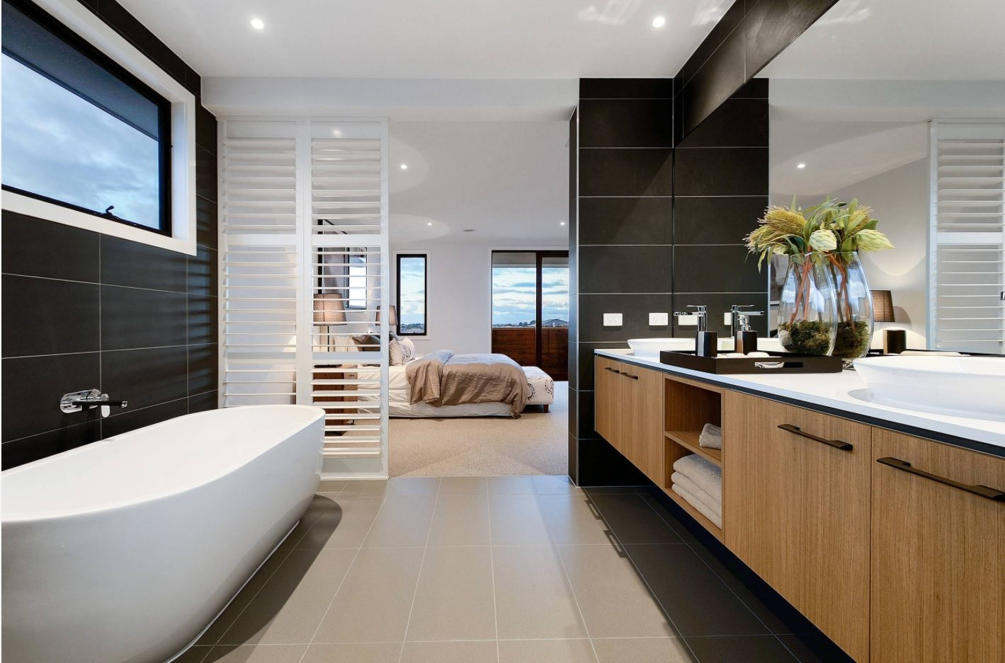 Hi-tech in the bathroom with black accents, wooden vanity and white oval bathtub