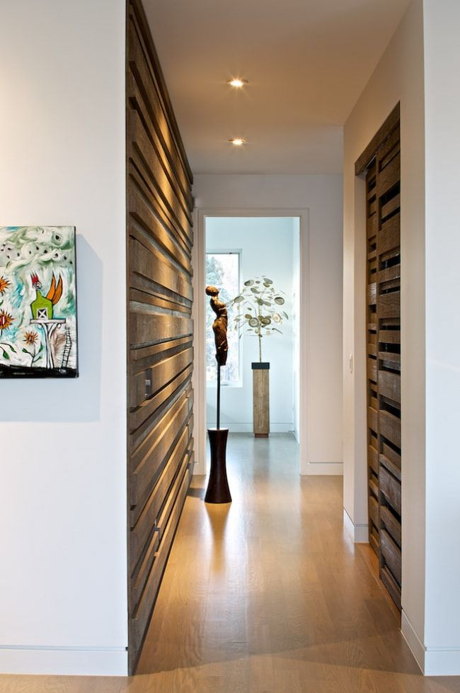 Intimate lighting and peculiar wooden structure of the surfaces in the narrow corridor