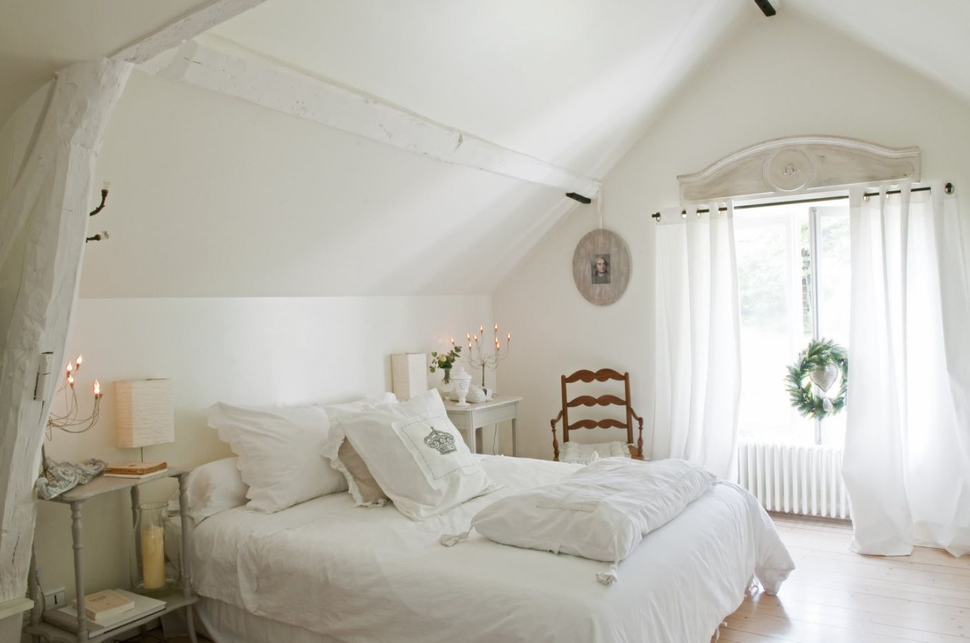 Slant of the ceiling in the light bedroom in creamy color scheme looks like decorative element