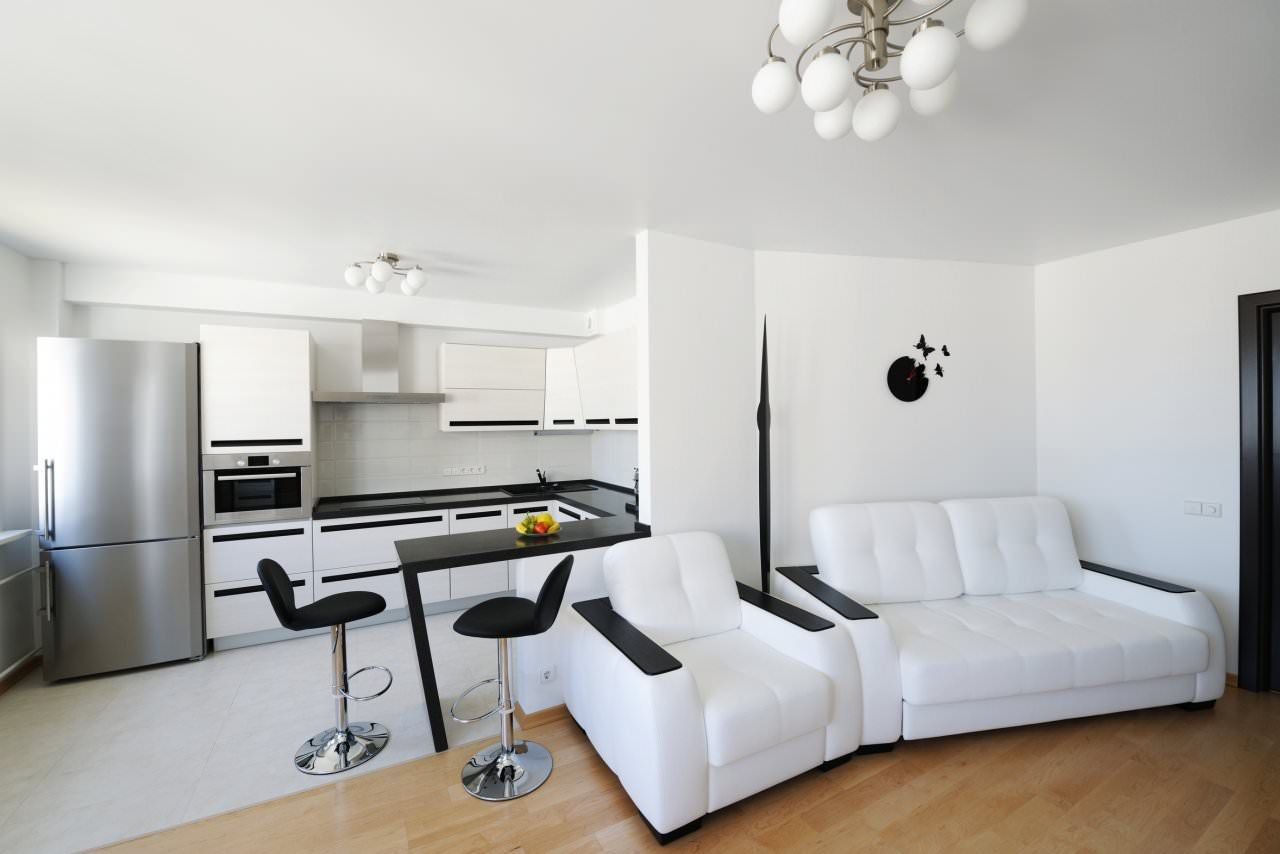Unusual hi-tech decor in contrasting black and white color scheme with improvised bar counter introducing dining zone