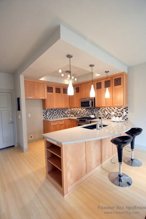 Kitchen with island dining zone trimmed with light wood