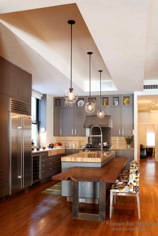 Ultramodern interior with pendant lamps and steel surfaces of appliances