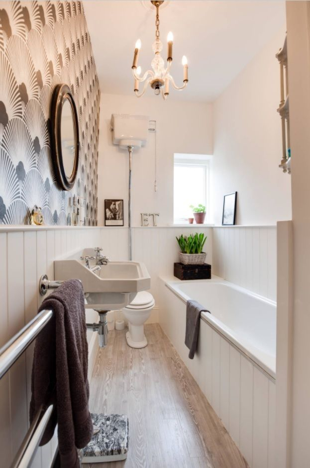 High mounted toilet bowl in a classic decorated bathroom interior with wainscoting and wallpapered walls