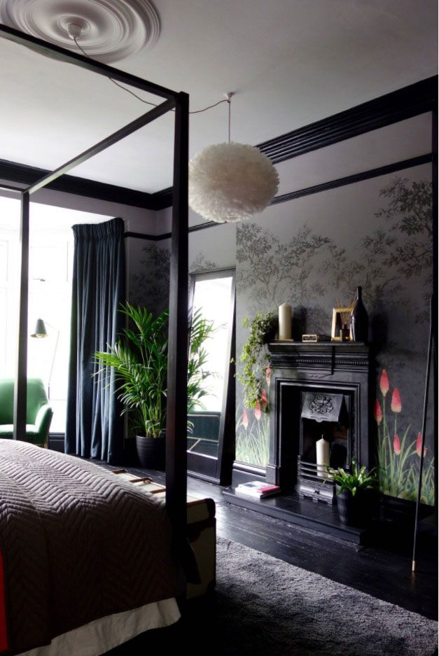 Gorgeous dark interior with canopy bed and a fireplace with mantelshelf stuffed with decorative elements
