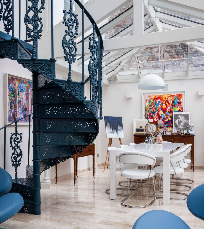 Spiral Staircase on dark steel carcass in the sunroom living with white decoration and furniture