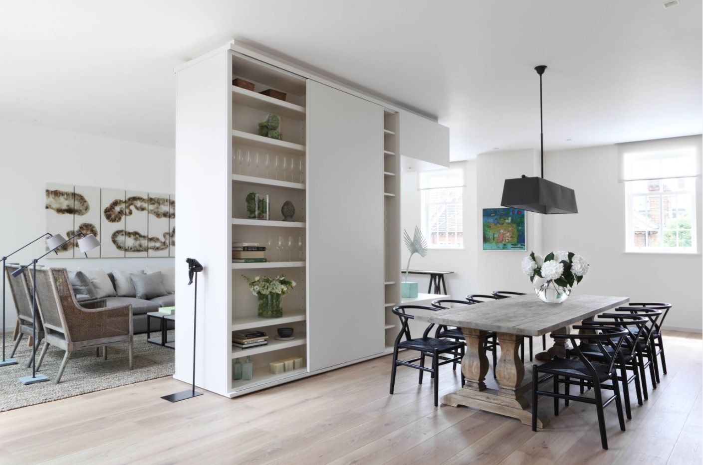 Dining Hall Furniture for Different Apartment Types. Light color theme in of the interior with dining zone seprated by shelving