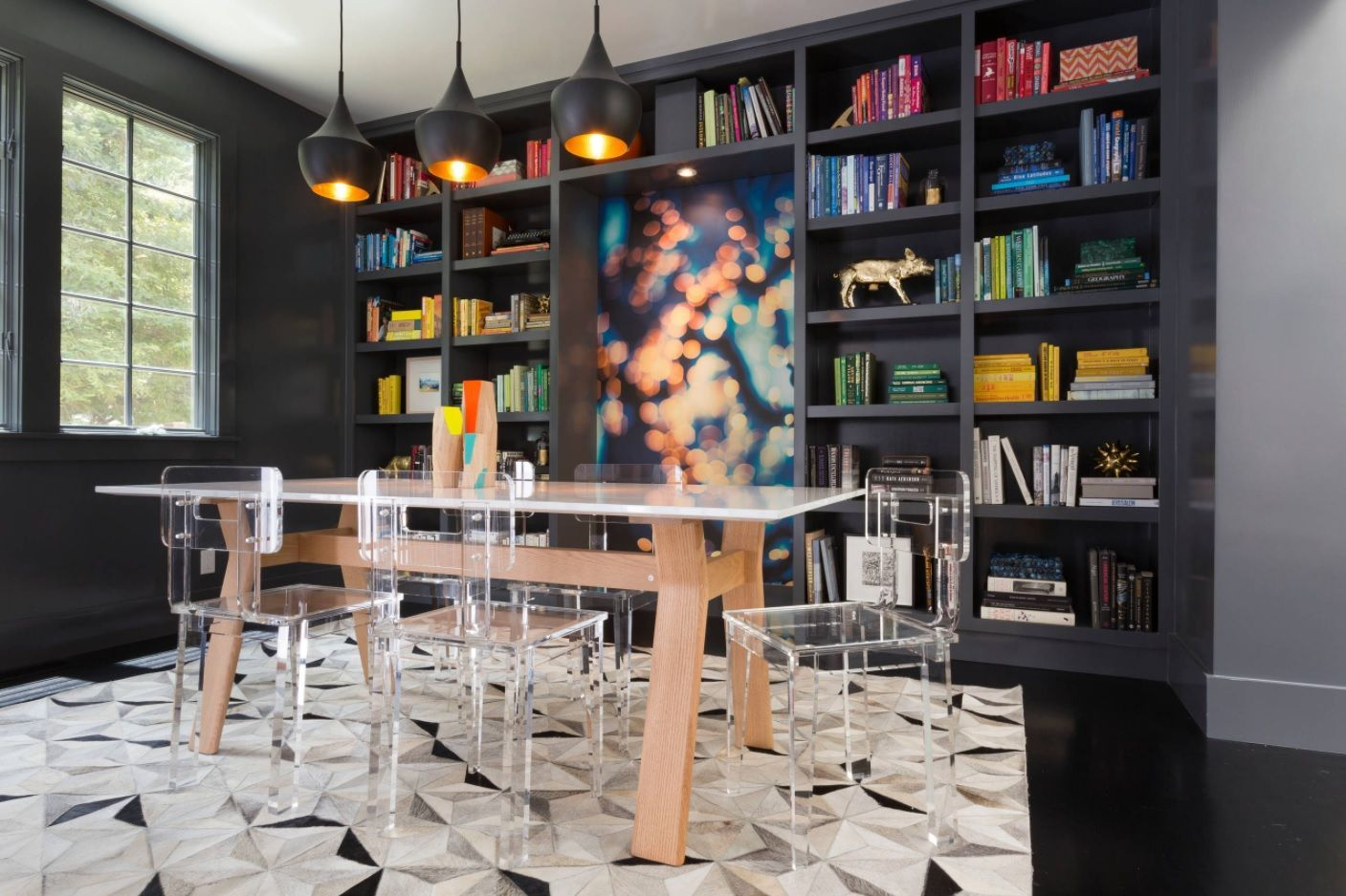Unusual designer's solution to put dining zone into the fusion decorated library in dark tones