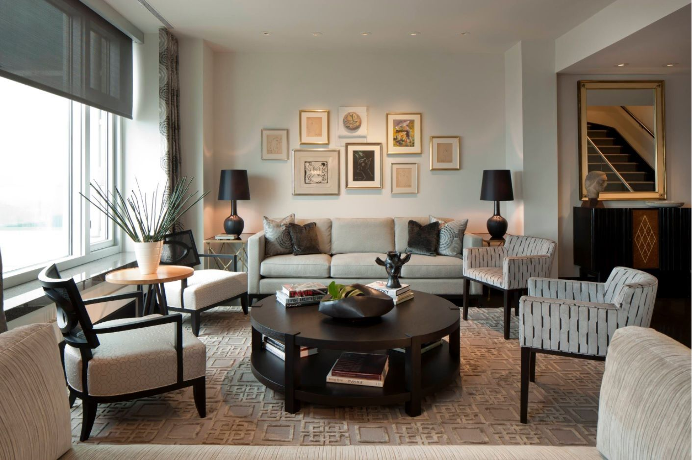 Living Room Layout Design & Decoration Ideas. Round dark coffee table in the room decorated with pictures