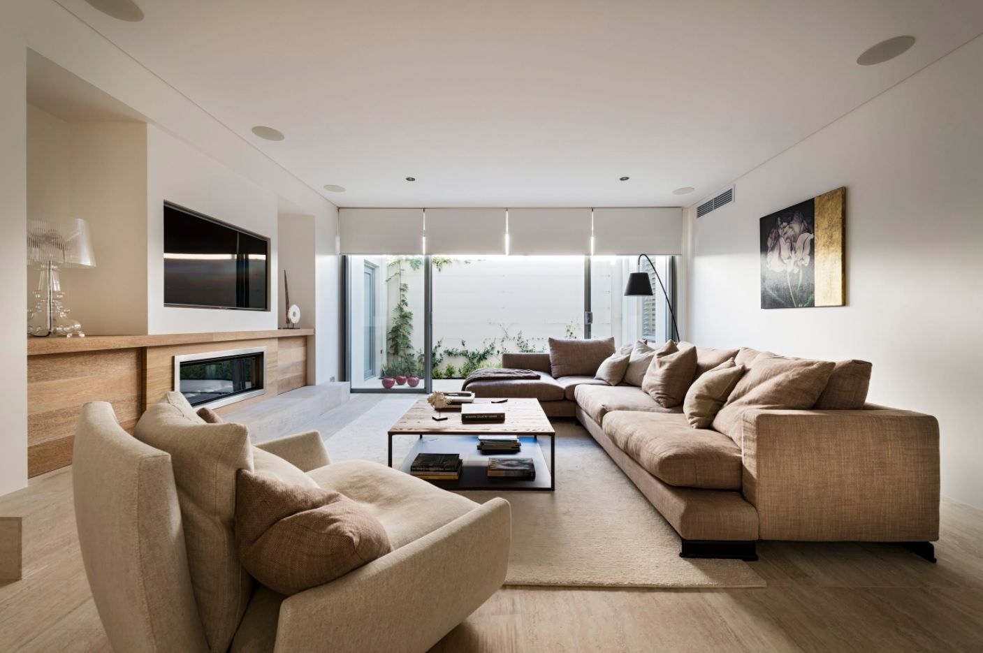 Brown upholstered sofas in the lounge room with metal framed coffee table