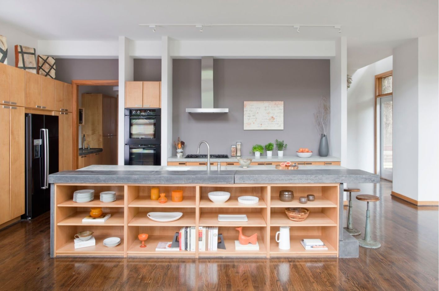 Open shelving of wood under island top in Modern open kitchen design