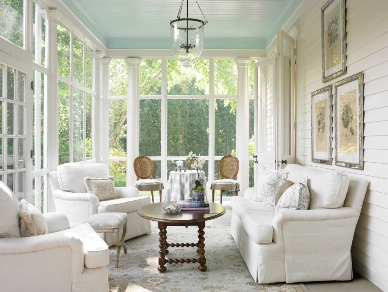 Classic interior in white with upholstered furniture and dark wooden coffee table