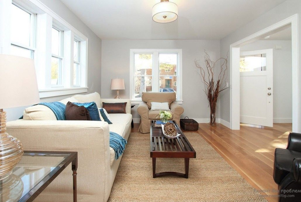 Cute interior design in gray color with natural floor and creamy tint of upholstered furniture