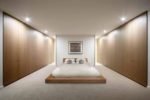 Unusual usage of mirrors to create the sensation of long room in the minimalistic bedroom