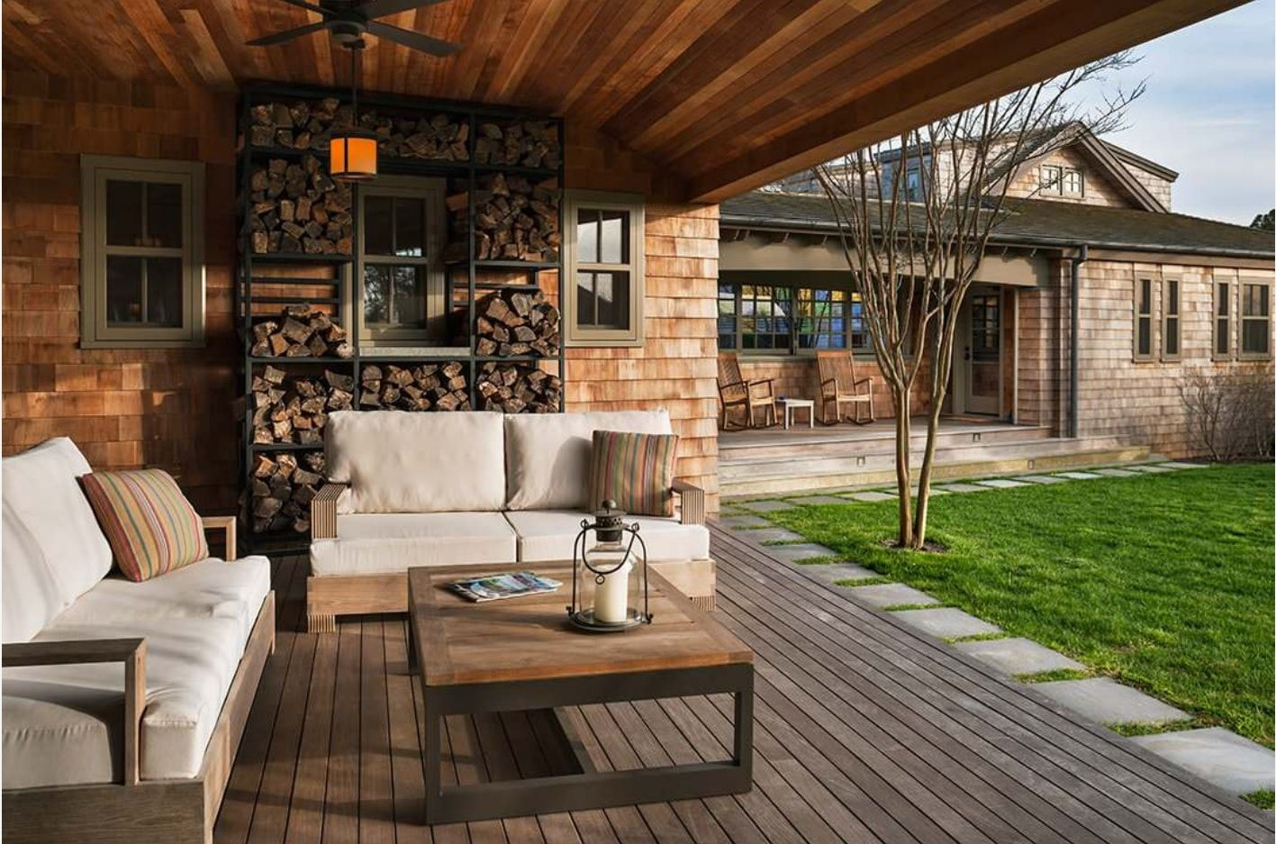 Outdoor patio zone under the shed with creative firewood racks and wooden made upholstered furniture