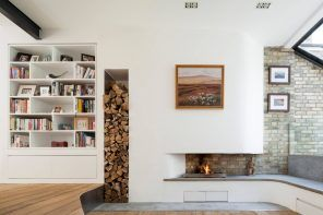 White matte living room interior in minimalistic Scandi style with hole for firewood in the wall near fireplace